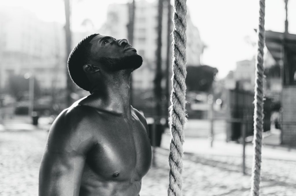A man trying to climb a rope as part of his workout