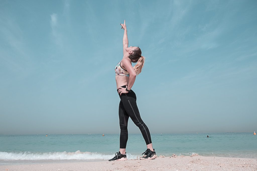 A fit woman pointing at the sky