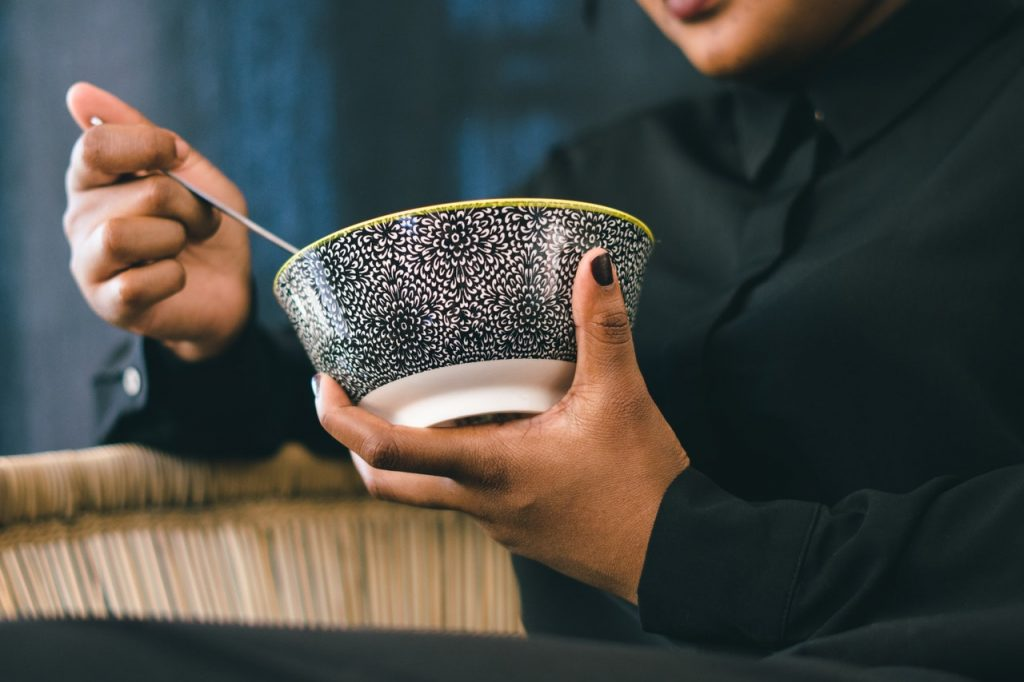 person holding a bowl of chinese food
